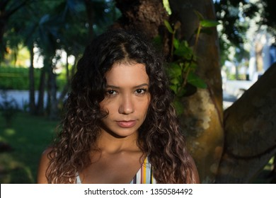 Close up portrait of pretty mexican young woman standing on the forest ,looking at the camera with a serious expression.