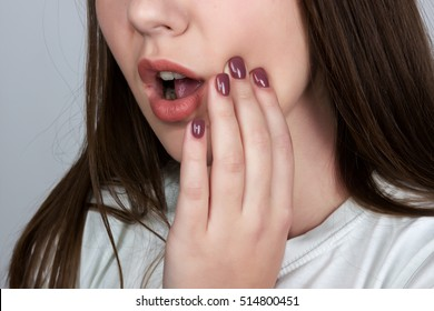 Close up portrait of a pretty woman having toothache  standing over gray background