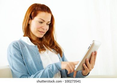 Close up portrait of a pretty young female working on tablet PC