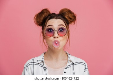 Close up portrait of a pretty young girl chewing bubble gum isolated over pink background