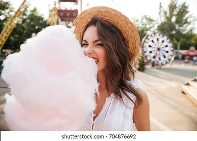 Close up portrait of a pretty young girl eating cotton candy at amusement park