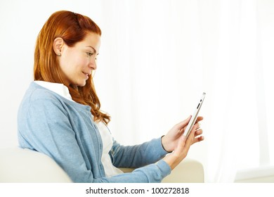 Close up portrait of a pretty young woman using a tablet PC on a light background