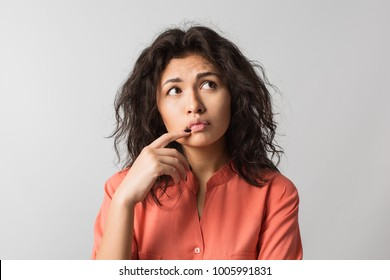 close up portrait of pretty young woman thinking about problem, confused emotion, isolated, wearing orange shirt, hipster style, curly hair, holding finger at lips, looking up, having idea