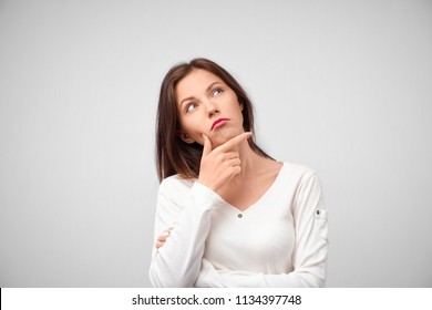 Close up portrait of pretty young woman thinking about problem, confused emotion, isolated, wearing white shirt, hipster style, dark hair, holding finger at lips, looking up, having idea.