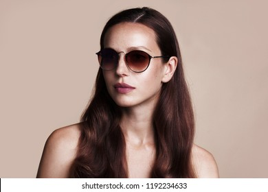Close up portrait of pretty young woman with glasses on gray background. Female fashion model posing with sunglasses.