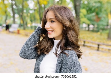 Close up portrait in profile of sensitive woman. She has dark short hair and wonderful big blue eyes. She is playfully looks at the camera. Background green park.