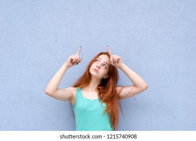 Close up portrait of red hair model standing on light blue background looking and pointing up with index fingers on your product. Copy space for text