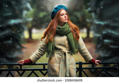 Close up portrait of a redhead  Beautiful girl in a green scarf and blue hat standing on colorful background. Art work of romantic woman .Pretty tenderness model looking afar