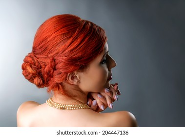 Close up portrait of a redhead woman with elegant braided hairstyle isolated over gray