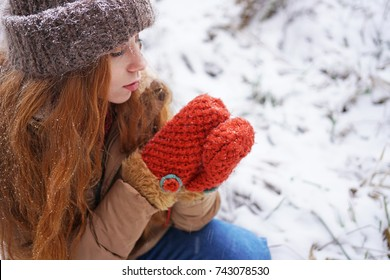 close up Portrait of redhead woman outdoor. Gorgeous young girl in fur winter knitted hat, red mittens. winter fashion. snowfall.Snowy grass on background. looking on mittens