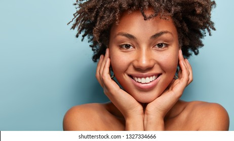 Close up portrait of relaxed black woman has gentle skin after taking shower, satisfied with new lotion, has no makeup, smiles tenderly, shows perfect teeth, stands shirtless against blue background