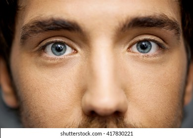 Close up portrait of relaxed handsome young man with grey eyes staring at camera. Studio, isolated on grey background.