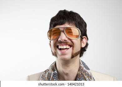 Close up portrait of a retro man in a 1970s leisure suit and sunglasses smiling and laughing
