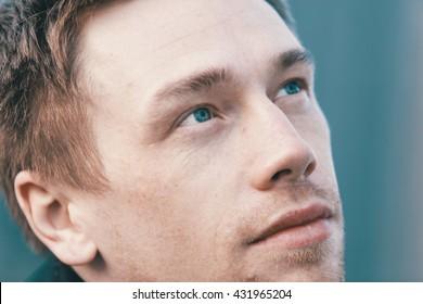 Close up portrait of romantic charismatic blonde man. looks into the distance. Cinema colour graded.