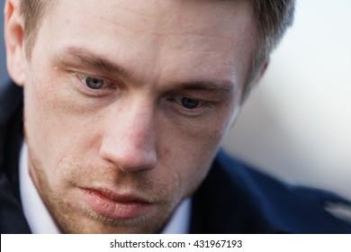 Close up portrait of romantic charismatic blonde man. pensive. looking down