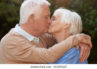 Close up portrait of romantic senior couple kissing while standing in each other's arms outside in park on a sunny day
