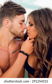 Close up portrait of romantic sensual  couple in love  kissing  . Sexy woman and handsome man posing on the beach .