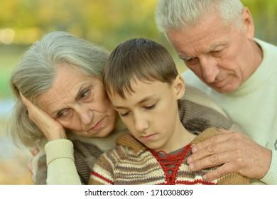 Close up portrait of sad grandfather, grandmother and grandson hugging in park