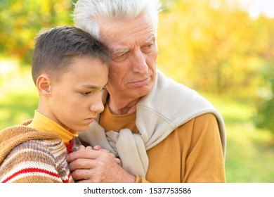 Close up portrait of sad grandfather and grandson hugging