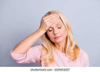 Close up portrait of sad upset unhappy beautiful lovely tender weak nervous feeling bad beautiful grandmother touching forehead with palm high temperature isolated on gray background