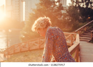 Close up portrait of a sad woman in a park on a warm summer day during the sunset