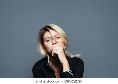 Close up portrait of a sad young woman, looking to the camera, holding hand near face, against a plain studio background