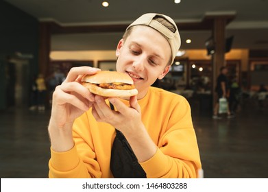 Close portrait of a satisfied boy with a burger in his hand, hungry looking at a sandwich and wants to eat it, background of a fast food restaurant in a shopping mall.Guy eats sandwich in a food court