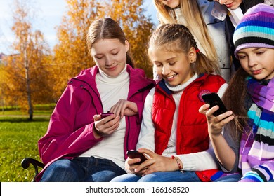 Close portrait of school age teen kids looking at their mobile phones sitting on the bench in autumn park on sunny day with smile on faces