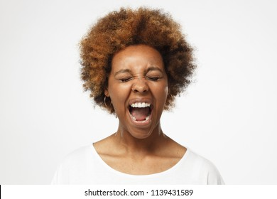 Close up portrait of screaming with closed eyes crazy african american woman in blank white t-shirt isolated on gray background