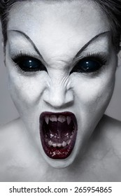 Close up portrait of a screaming undead girl with sharp teeth, white skin and black eyes