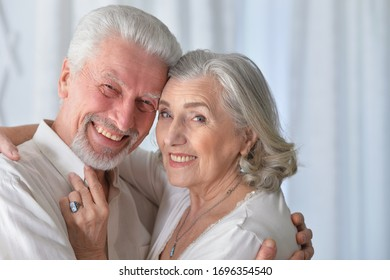 Close up portrait of senior couple hugging at home