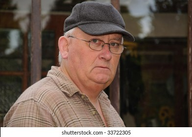 close up portrait of senior male glasses and cap