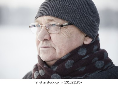 Close up portrait of senior man wearing glasses, knit cap and scarf standing outdoors in winter