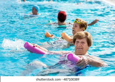 Close up portrait of senior woman doing body exercise with friends at aqua gym session in outdoor pool.