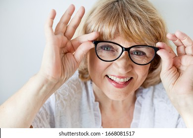 Close up portrait of a senior woman looking at her glasses in surprise, opening her mouth and opening her eyes wide over a white background, smiling