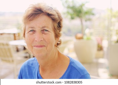 close up portrait of senior woman sitting in outdoor summer cafe
