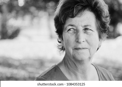 close up portrait of senior woman walking on the summer green park