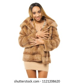Close up portrait of sensual young african woman in beige fur coat and dress. Studio shot of woman against white background.