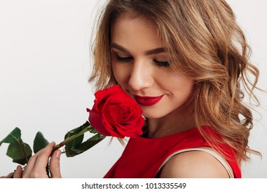 Close up portrait of a sensual young woman dressed in red dress holding a rose isolated over white background