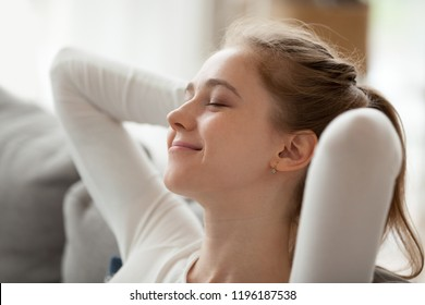 Close up portrait serene woman smiling sitting on couch at home. Girl has a break after work or study closing eyes putting hands behind head relaxing thinking, feels happy breathing fresh air concept