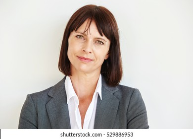 Close up portrait of serious business woman standing by white wall