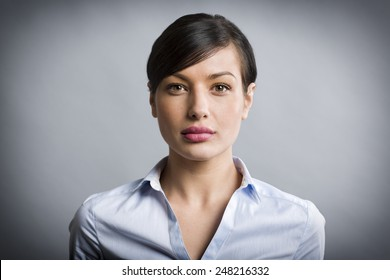 Close up portrait of serious, confident businesswoman looking straight, isolated on grey background.