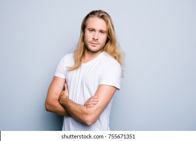 Close up portrait of serious and confident young guy with bristle and long blonde hair, he is standing with crossed arms over grey shadeless background