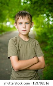 Close up portrait of serious little boy with folded hands outdoo