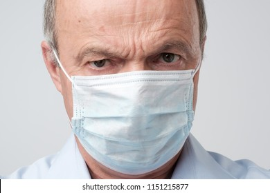 Close up portrait of serious man in special medic mask. He is looking serious. Mature experienced doctor. Medicine, healthcare and emergency in hospital