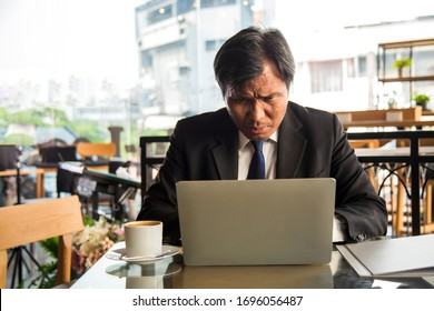 Close up portrait serious middle age Asian businessman using a laptop with coffee cup at side at modern office.