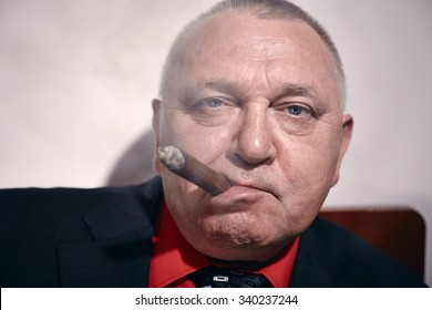 Close up portrait of serious middle aged businessman wearing black suit and red shirt smoking cigar in office