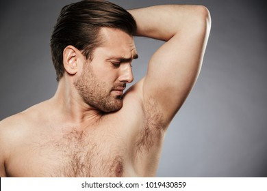 Close up portrait of a serious shirtless man smelling his armpit isolated over gray background
