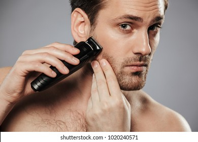 Close up portrait of a serious shirtless man shaving beard with an electric razor isolated over gray background