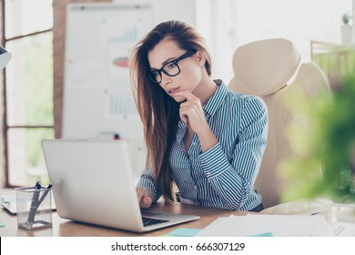 Close up portrait of serious young business lady economist in formal wear and with glasses, sitting at her work station and concentrated on work